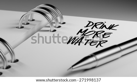 Closeup of a personal agenda setting an important date writing with pen. The words Drink more water written on a white notebook to remind you an important appointment. - stock photo