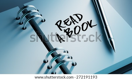 Closeup of a personal agenda setting an important date writing with pen. The words Read a book written on a white notebook to remind you an important appointment. - stock photo