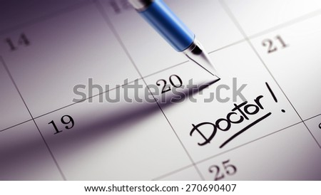 Closeup of a personal agenda setting an important date written with pen. The words Doctor written on a white notebook to remind you an important appointment. - stock photo