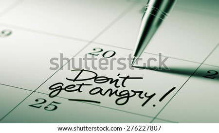Closeup of a personal agenda setting an important date written with pen. The words Don't get angry written on a white notebook to remind you an important appointment. - stock photo