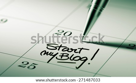 Closeup of a personal agenda setting an important date written with pen. The words Start my Blog written on a white notebook to remind you an important appointment. - stock photo
