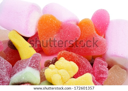 closeup of a pile of different candies, with a pair of heart-shaped candies in the center - stock photo