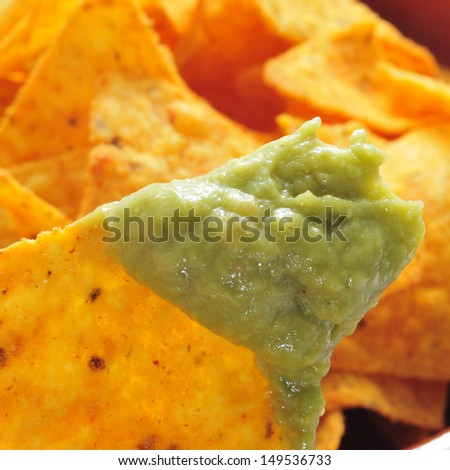 closeup of a pile of nachos and guacamole - stock photo