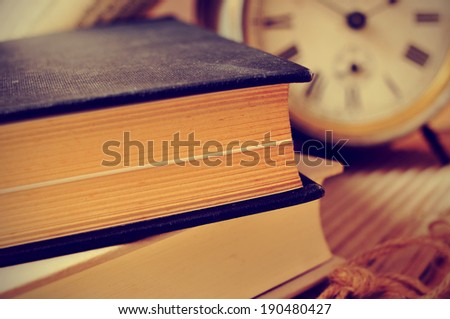 closeup of a pile of old books and an old alarm clock on a desk, with a retro effect - stock photo