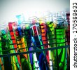 closeup of a pile of test tubes with liquids of different colors - stock photo