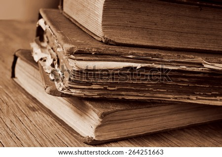 closeup of a pile of worn-out old books on a rustic wooden table, in sepia toning - stock photo