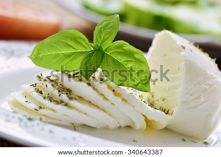 closeup of a plate with a sliced fresh cheese - stock photo
