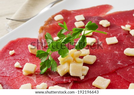 closeup of a plate with beef carpaccio served with parmesan cheese - stock photo