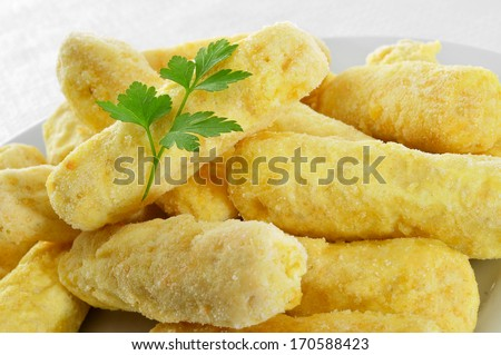closeup of a plate with some frozen fish sticks ready to be cooked - stock photo