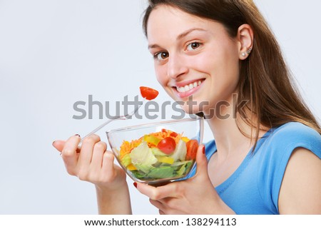 Closeup of a pretty young woman eating a vegetable salad - stock photo