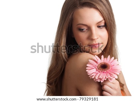 closeup of a pretty young woman smelling a pink flower - stock photo