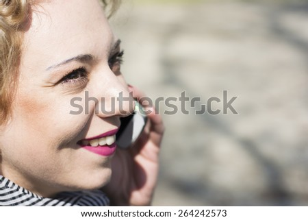 Closeup of a pretty young woman with blond curly hair talking on the phone.She is smiling as she is communicating with her friends. - stock photo