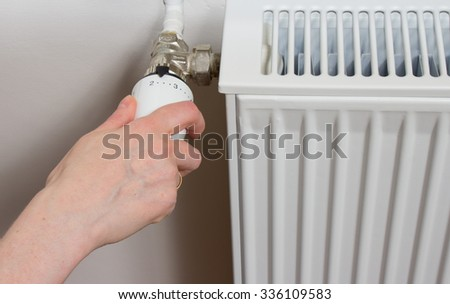 Closeup of a radiator thermostat with woman hand - stock photo