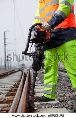 closeup of a railroad worker and a machine - stock photo
