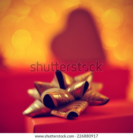 closeup of a red gift box with a golden ribbon bow and some gifts in the background - stock photo