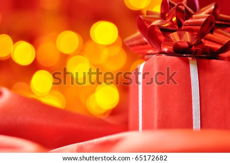 closeup of a red gift box with blurred lights on background - stock photo