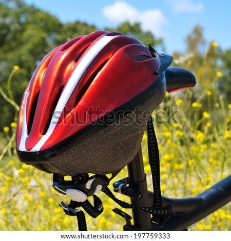 closeup of a red helmet hanging on a mountain bike in a spring landscape - stock photo