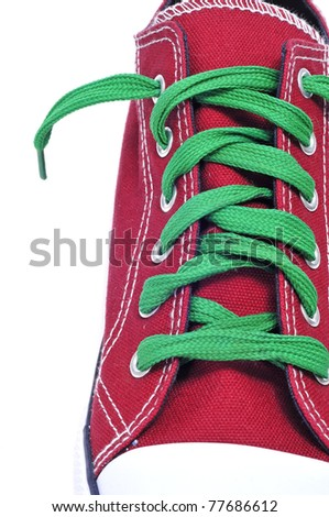 closeup of a red sneaker with green shoelaces on a white background - stock photo