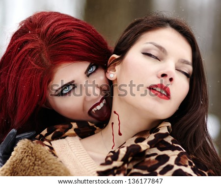 Closeup of a redheaded vampire biting innocent girl - stock photo