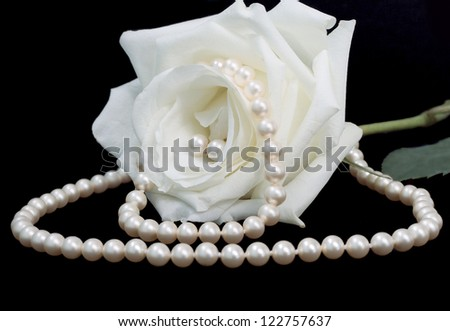 closeup of a rose with pearl set - earrings, bracelet and necklace - on the black background - stock photo