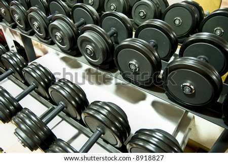 Closeup of a row of free weights in the gym - stock photo
