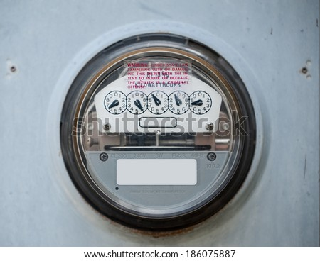 Closeup of a scratched up electric meter in use - stock photo