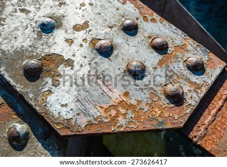 Closeup of a section of a historic railroad bridge with large rusting rivets on a sunny day. - stock photo