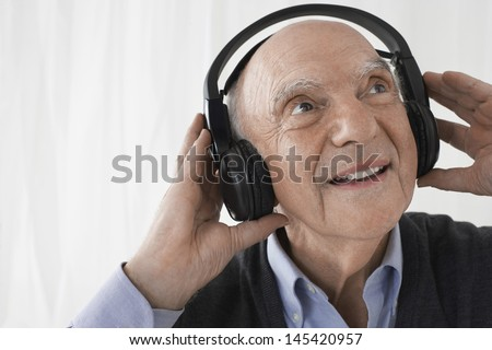 Closeup of a senior businessman wearing headphones against white background - stock photo