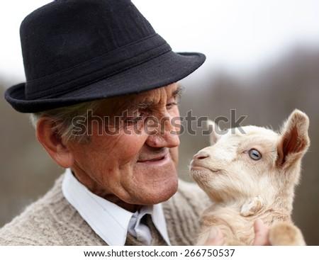 Closeup of a senior man holding a cute baby goat outdoor - stock photo