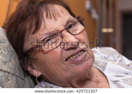 Closeup of a senior woman grimacing and frowning. - stock photo