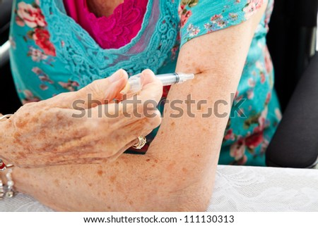Closeup of a senior woman's hands as she gives herself a shot in the arm. - stock photo