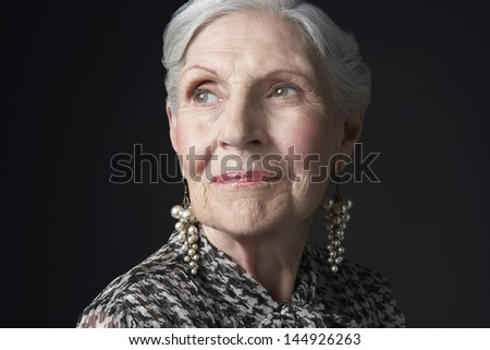 Closeup of a senior woman with pearl earrings looking up against black background - stock photo