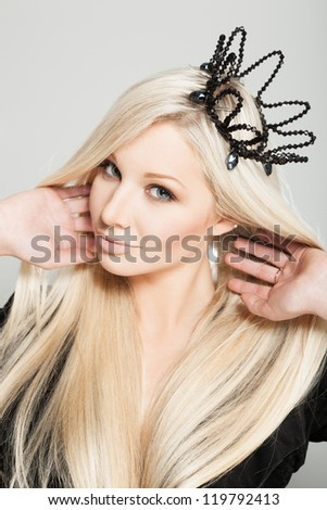 Closeup of a sensual woman with black crown, indoors - stock photo