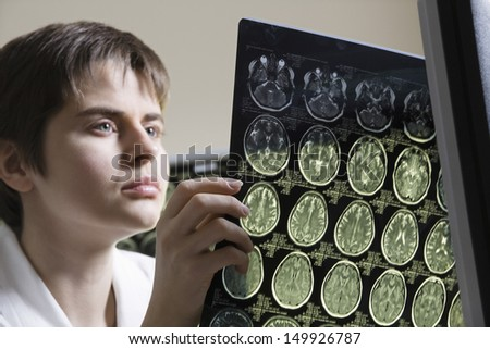 Closeup of a serious female doctor holding CAT scan - stock photo