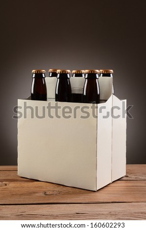 Closeup of a six pack of brown beer bottles on a rustic wooden table. Vertical format with a light to dark gray spot background. - stock photo