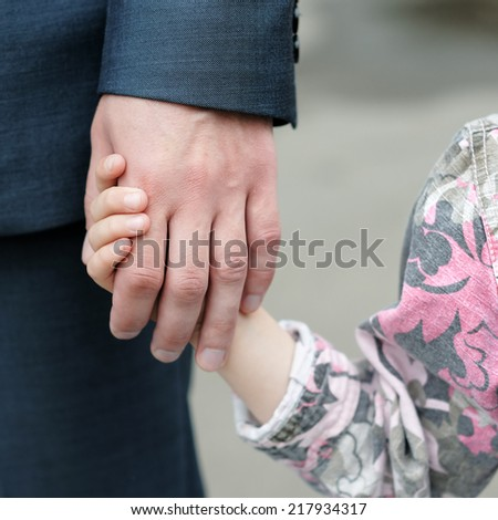 Closeup of a small girl holding a man's hand  - stock photo