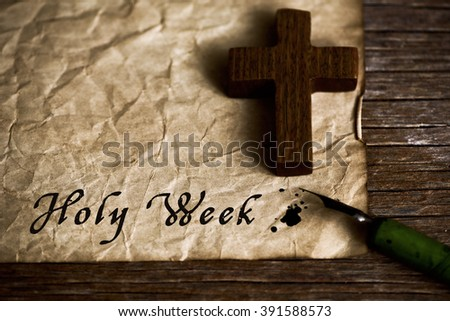 closeup of a small wooden christian cross, an old dip pen and a yellowish paper with the text holy week written with black ink in it, on a rustic wooden table - stock photo