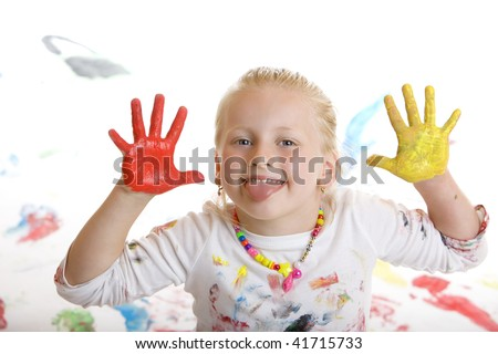 Closeup of a smiling child with painted hands making a grimace - stock photo