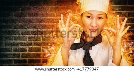 Closeup of a smiling female cook gesturing okay sign against image of a wall - stock photo