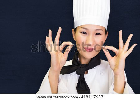 Closeup of a smiling female cook gesturing okay sign against navy blue - stock photo