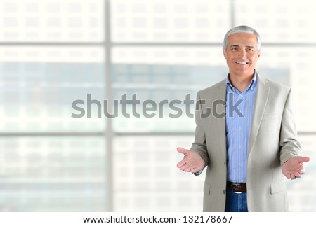 Closeup of a smiling middle aged businessman gesturing with both hand. Man is standing in front of a large modern office building window. Horizontal Format. - stock photo