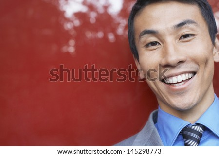 Closeup of a smiling young businessman against red - stock photo