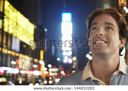 Closeup of a smiling young man in Times Square New York at night - stock photo