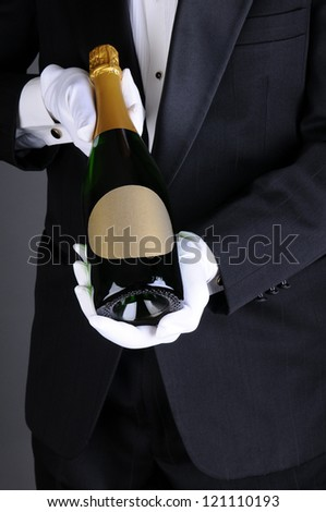 Closeup of a Sommelier in a tuxedo presenting a champagne bottle, Vertical format over a light to dark gray background. Man is unrecognizable. - stock photo