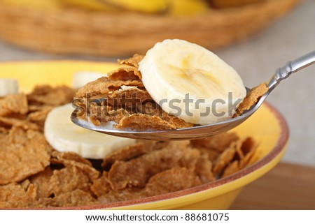 Closeup of a spoonful of wheat flake cereal and banana slice - stock photo