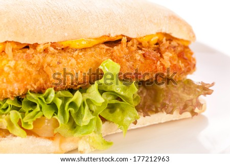 Closeup of a tasty burger with a golden crispy crumbed chicken breast topped with melted cheese and fresh curly lettuce on a white crusty roll - stock photo