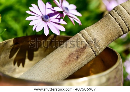 closeup of a tibetan singing bowl surrounded by pink wildflowers - stock photo