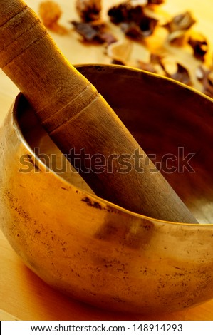closeup of a tibetan singing bowl with its mallet - stock photo