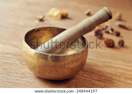 closeup of a tibetan singing bowl with its mallet on a table with dried flowers - stock photo