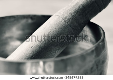 closeup of a tibetan singing bowl with its wooden mallet, in duotone - stock photo